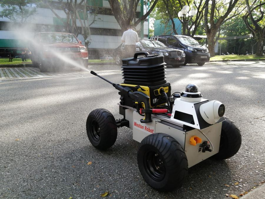 The Weston Robot protype on a paved street, actively spraying outside. Cars and a person in the background of the image.