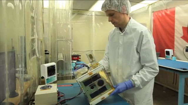 University of Toronto students use a thermal chamber to test nanosatellite components in temperature ranges encountered in space.